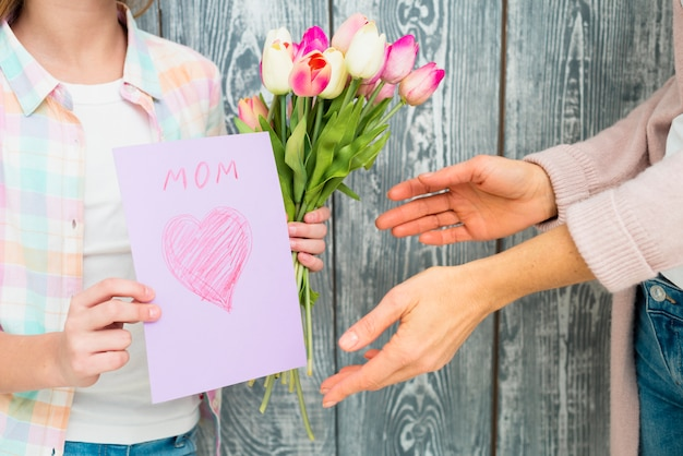 Dia das mães de cartão postal e tulipas nas mãos da menina