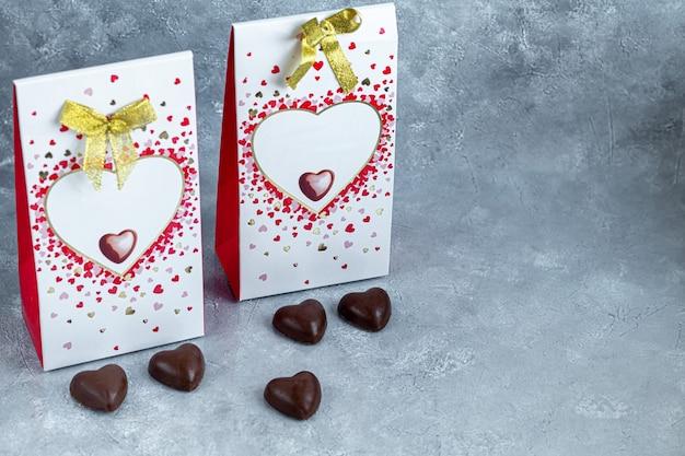 Dia das mães, dia da mulher, dia dos namorados ou aniversário em fundo cinza. presentes, doces em forma de coração. copie o espaço.