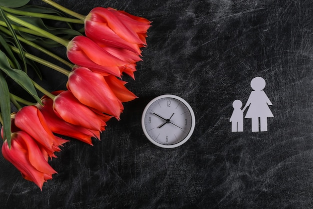 Dia das mães, dia do conhecimento. mãe de papel com seu filho, um buquê de tulipas vermelhas no fundo de um quadro de giz escolar