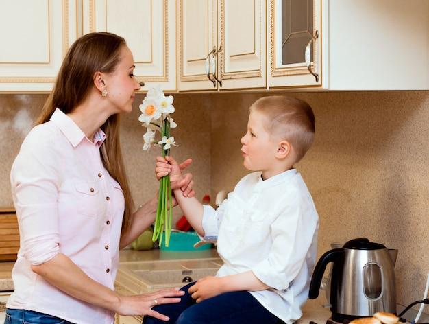 Dia das mães, feriados e conceito de família - filho pequeno feliz dá flores para sua mãe sorridente em casa. uma criança dá à mãe um buquê de narcisos