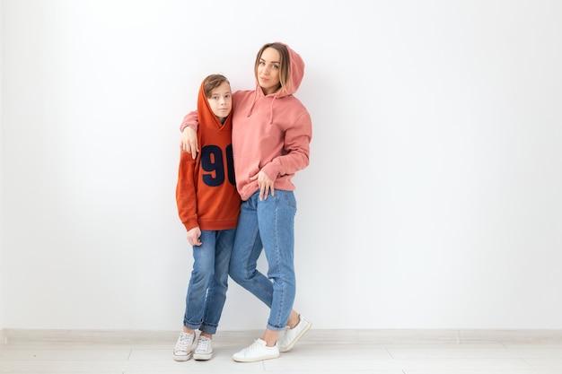 Dia das mães, filhos e conceito de família - menino adolescente abraçando sua mãe na parede branca com uma cópia
