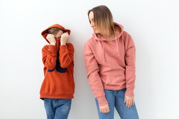 Dia das mães, filhos e conceito de família - menino adolescente abraçando sua mãe na parede branca
