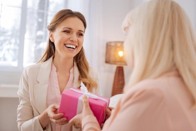 Dia das mães. jovem alegre e encantada segurando um presente e se entregando à mãe enquanto a parabeniza pelo feriado