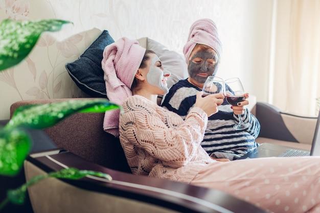Dia das mães. mãe e filha adulta aplicaram máscaras faciais em casa. mulheres relaxando enquanto toma vinho