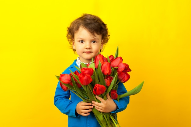 Dia das mães. menino bonito criança encaracolado com um buquê de flores. um buquê de tulipas vermelhas nas mãos