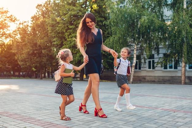 Dia das mães. mulher feliz conhecendo as filhas dos filhos depois das aulas ao ar livre da escola primária. a família vai para casa de mãos dadas.