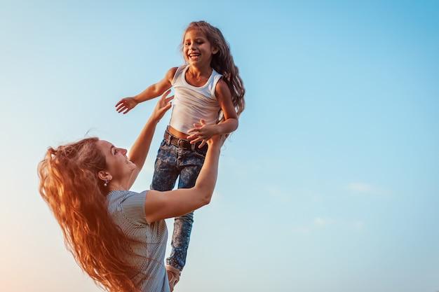 Dia das mães. mulher jogando se divertindo com a filha no parque primavera. mãe jogando garota ao ar livre e rindo. família