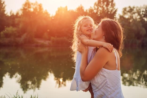 Dia das mães. mulher jogando se divertindo com a filha pelo rio verão ao pôr do sol. mulher segurando criança e rindo. família