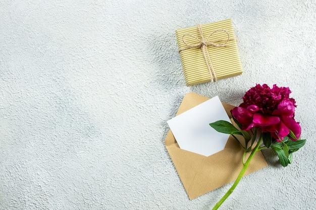 Dia das mães ou conceito de dia das mulheres. peônia de borgonha e cartão de nota vazio para o texto no fundo concreto. vista superior, configuração plana, cópia espaço