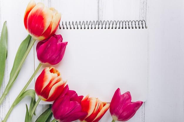 Dia das mães. tulipas e caderno cor-de-rosa com espaço da cópia.