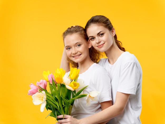 Dia das mães, uma jovem mulher com filha posando com flores, um presente para o dia da mulher e o dia das mães