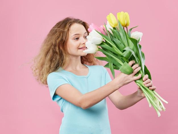 Dia das mães, uma jovem mulher com uma criança posando com flores, um presente para o dia da mulher e o dia das mães