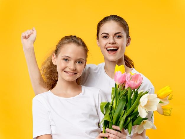 Dia das mães, uma jovem mulher com uma criança posando com flores, um presente para o dia das mães