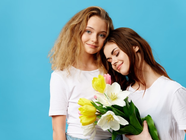 Dia das mães, uma jovem mulher com uma criança posando no estúdio com flores, um presente para o dia da mulher e o dia das mães