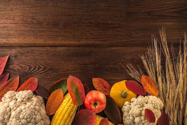 Dia de ação de graças. composição com legumes e folhas de outono no fundo escuro de madeira com copyspace