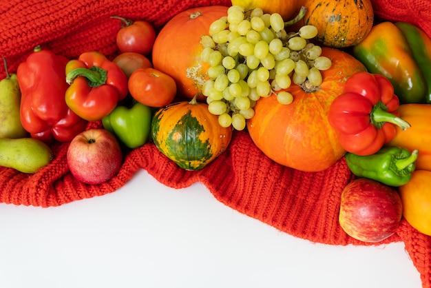 Dia de ação de graças. grande colheita de outono - pêra, maçãs, abóbora, pimenta, tomate em um fundo branco e um pano vermelho. conceito de celebração de ação de graças, vista superior.
