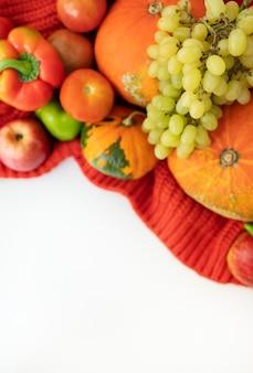 Dia de ação de graças. pêra colheita de outono, maçãs, abóbora, pimenta, tomate em um fundo branco e um pano vermelho.