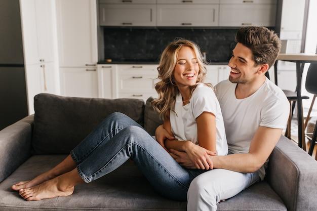 Dia de alegria juntos em apartamentos aconchegantes e aconchegantes. feliz cara atraente com linda garota, olhando uns aos outros, rindo e se abraçando no sofá.