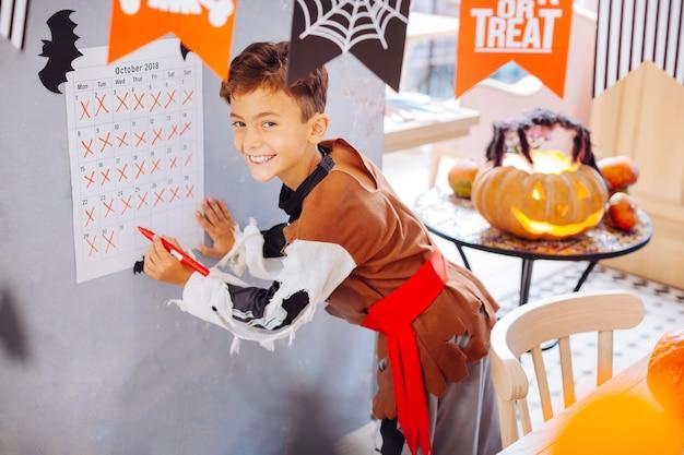 Dia de celebração. garoto bonito radiante usando fantasia de halloween e se sentindo extremamente feliz no dia de comemoração
