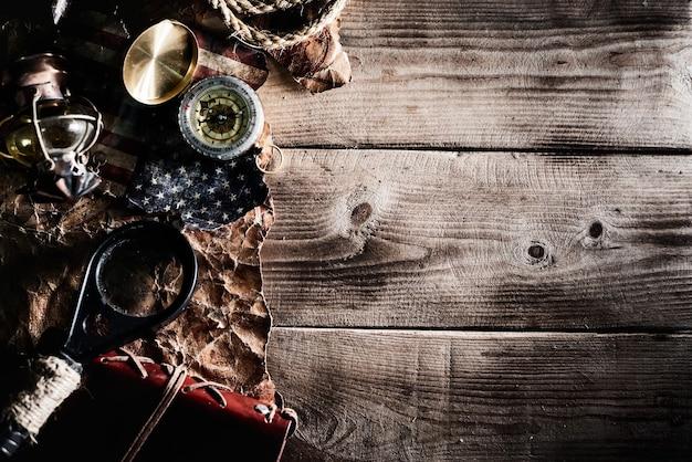 Dia de colombo. piratas e tesouros com mapa-múndi e equipamentos de descoberta. copie o espaço em fundo escuro.