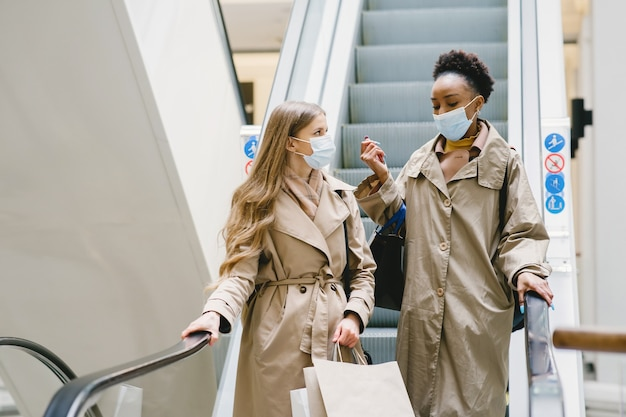 Dia de compras. conceito de coronavírus. mulheres com máscaras médicas.
