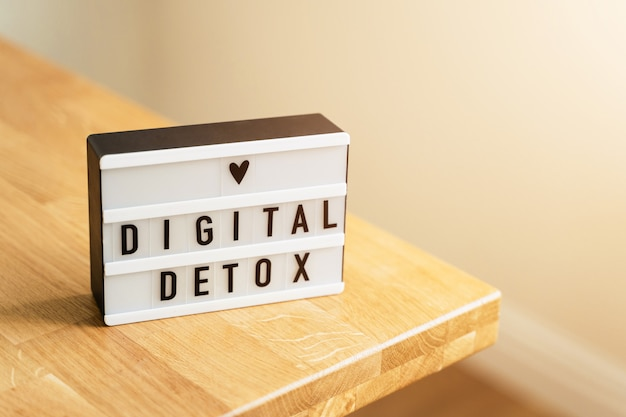 Dia de desintoxicação digital. lightbox na superfície de madeira e paredes brancas. proibição de gadgets