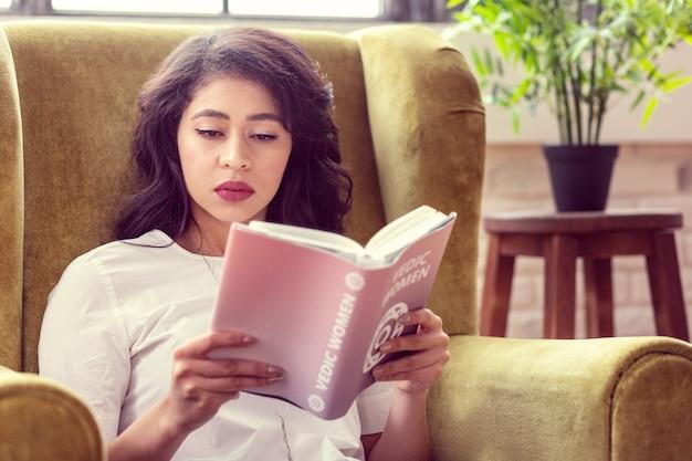 Dia de folga. mulher bonita e bonita lendo um livro enquanto relaxa em casa