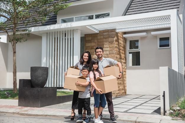 Dia de mudança. feliz família asiática na frente de sua nova casa