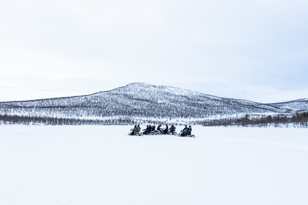 Dia de neve com pessoas andando de snowmobiles ao longe no norte da suécia