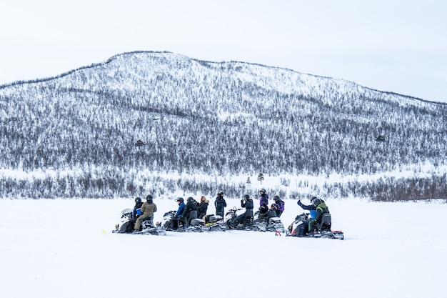 Dia de neve com pessoas andando de snowmobiles e uma montanha ao longe no norte da suécia