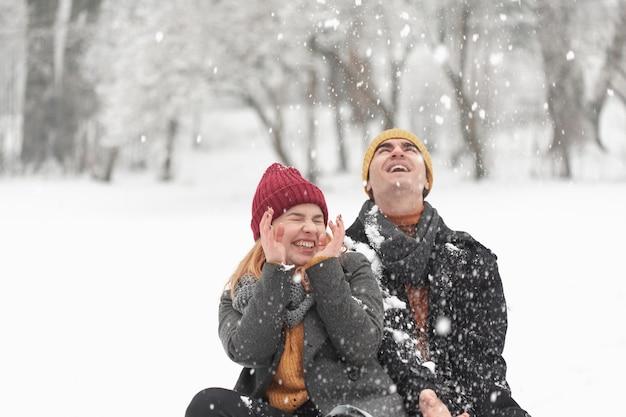 Dia de neve e casal no parque