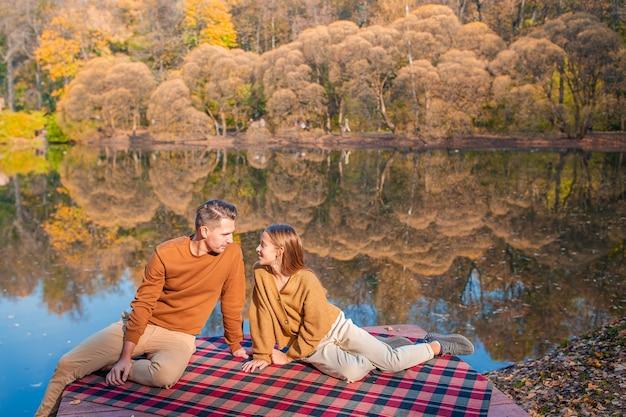 Dia de outono em família. jovem pai e sua filha juntos no parque outono