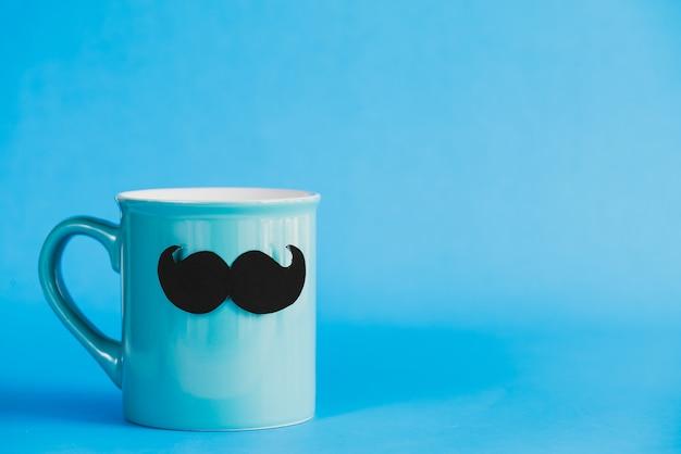 Dia de pais feliz, bigode no copo de café pastel ciano no fundo azul.