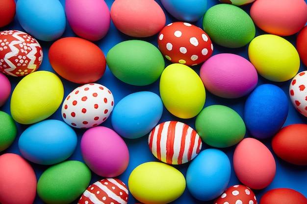 Dia de páscoa. fundo colorido decorado de ovos de páscoa. ovos de galinha pintados, vista superior