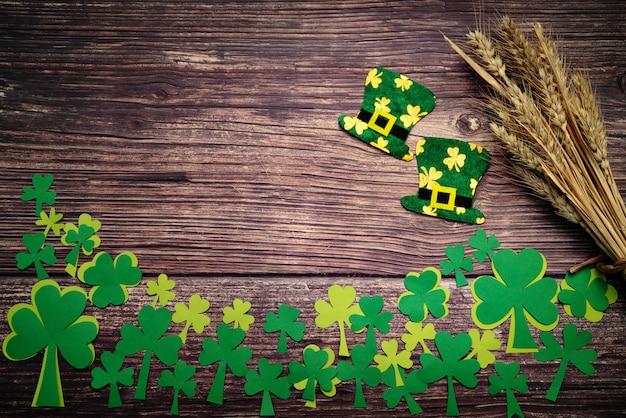 Dia de são patrício, moedas de ouro, chapéu festivo e verde trevos em madeira