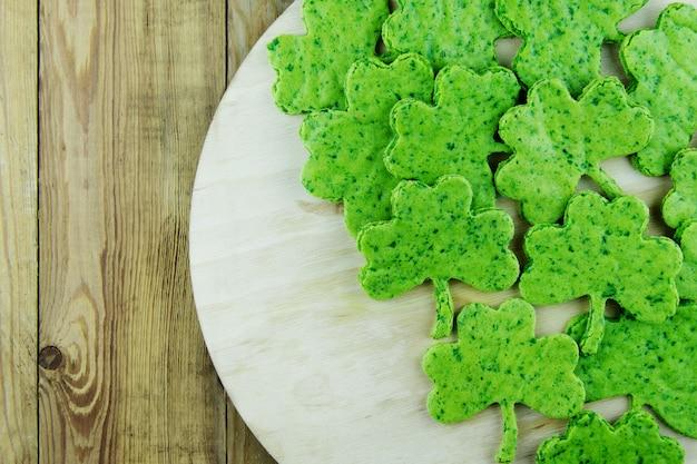 Dia de são patricio. petisco verde do biscoito sob a forma da folha do trevo em um fundo de madeira. copie o espaço