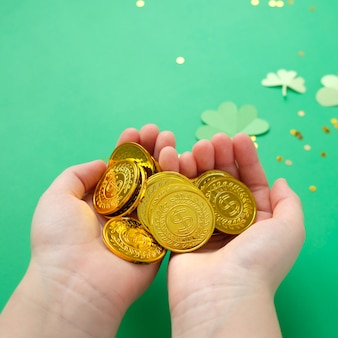 Dia de são patrício, trevo e moedas de ouro sobre fundo verde