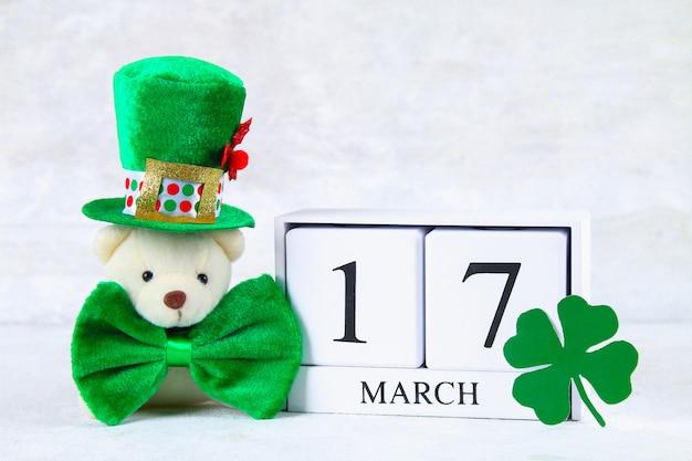 Dia de são patricio. um calendário de madeira mostrando 17 de março. chapéu verde e arco.
