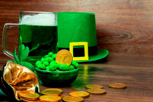 Dia de são patrick. caneca de vidro verde de cerveja, doces de biscoitos de petiscos verdes, chapéu verde de duende, trevo de três pétalas verde e moedas de ouro na mesa de madeira