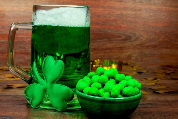 Dia de são patrick. caneca de vidro verde de cerveja, doces de biscoitos lanches verdes, trevo de três pétalas verde e moedas de ouro na mesa de madeira