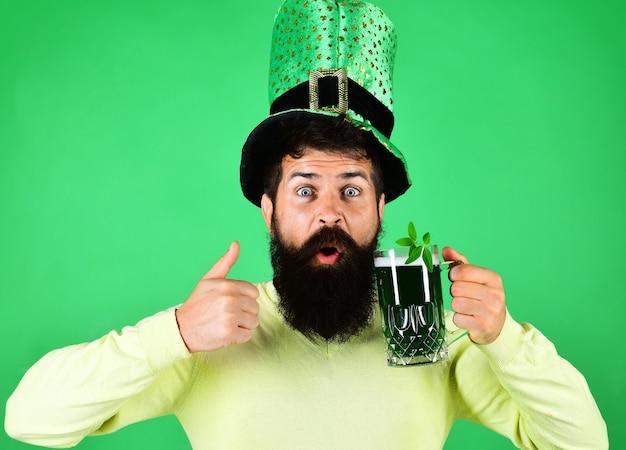 Dia de são patrick. homem barbudo com copo de cerveja mostra bom sinal. trevo na tradição da caneca irlandesa.