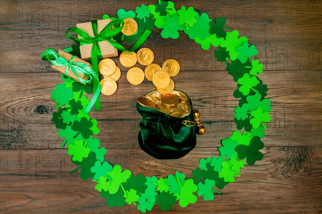 Dia de são patrick. pequeno saco de duende com moedas de ouro, deitado na mesa de madeira em forma de círculo de trevos de três pétalas verdes
