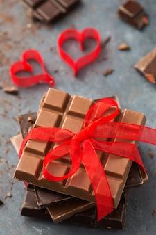 Dia de são valentim. chocolate amarrado com uma fita vermelha e corações na mesa cinza