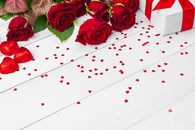 Dia de são valentim. rosas vermelhas e caixa de presente na mesa de madeira