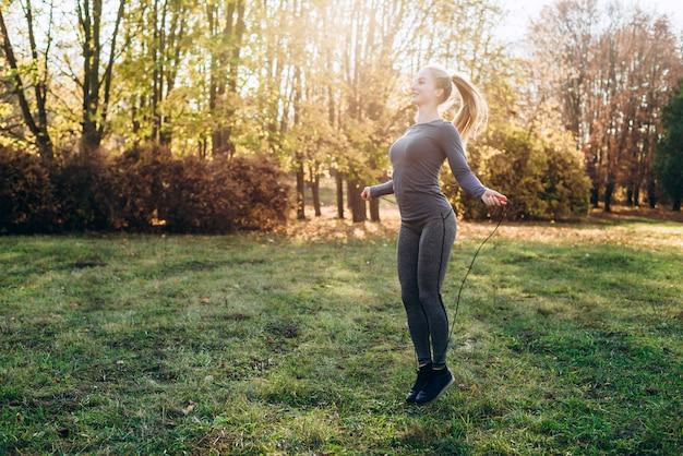 Dia de sol, a garota no parque pula em uma corda de pular.