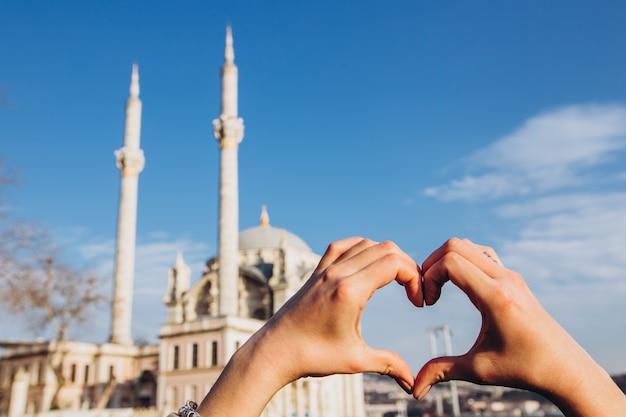 Dia de sol com céu azul. istambul, turquia. sultan ahmet mosque em um dia ensolarado. mulher bonita fazendo formato de coração com vista para a mesquita suleymaniye istambul.