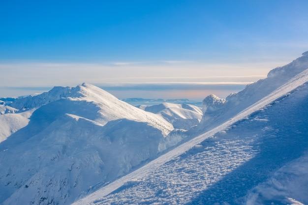 Dia de sol de inverno. picos de montanhas e céu azul. uma pista de esqui íngreme desce em primeiro plano