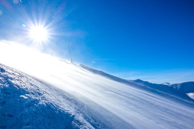 Dia de sol de inverno. pista de esqui vazia. um vento forte levanta uma grande quantidade de poeira de neve que brilha ao sol