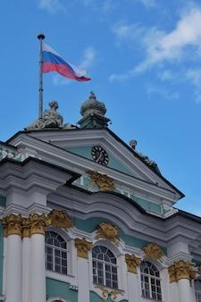 Dia de sol em são petersburgo com a bandeira russa hasteada acima da fachada do museu estatal hermitage