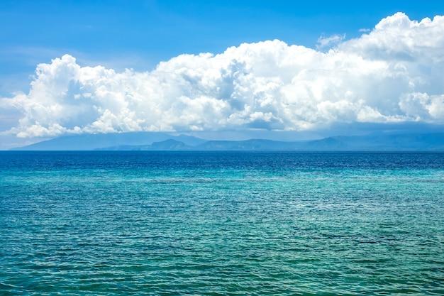 Dia de sol na indonésia. água turquesa do oceano calmo. nuvens surpreendentemente bonitas na costa distante